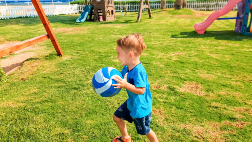 Portrait of happy smiling little boy holding ball in hands and running on grass at children playground